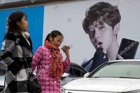 Chinese women walk past advertisement featuring teen idol Lu Han, also known as China's Justin Bieber in Beijing, China. China works to stifle celebrities as it seeks to dictate the values the nation's youth should embrace. It's part of the most ambitious effort in years to shape the country's booming entertainment industry. Instead of selfish, rich stars, the state is promoting performers who are all about patriotism, purity and other values that support the party's legitimacy, whether in movies about revolutionary heroes or through rap music