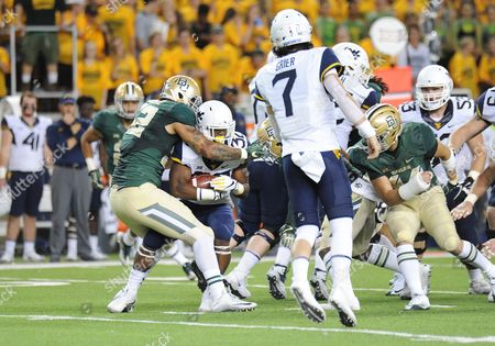 Stock Picture of Baylor Bears defensive end Greg Roberts (52) tackles West Virginia Mountaineers running back Martell Pettaway (32) during the 1st half of the NCAA Football game between the Baylor Bears and West Virginia Mountaineers at McLane Stadium in Waco, Texas