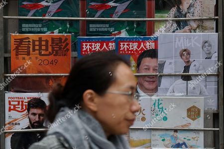 A woman walks by magazines featuring Chinese President Xi Jinping placed next the one featuring teen idol Lu Han, right, also known as China's Justin Bieber, at a news stand in Beijing, . China is working to stifle celebrities as it seeks to dictate the values the nation's youth should embrace. It's part of the most ambitious effort in years to shape the country's booming entertainment industry. Instead of selfish, rich stars, the state is promoting performers who are all about patriotism, purity and other values that support the party's legitimacy, whether in movies about revolutionary heroes or through rap music. The results have at best been mixed and at worst out of touch