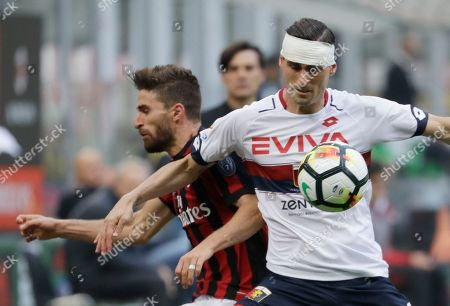 AC Milan's Fabio Borini, left, challenges for the ball with Genoa's Aleandro Rosi during a Serie A soccer match between AC Milan and Genoa, at the San Siro stadium in Milan, Italy