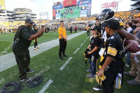 Pittsburgh Steelers Hall of Fame running back Jerome Bettis, left, takes a picture of Steelers wide receiver Antonio Brown with a group of young fans during warm ups before an NFL football game against the Cincinnati Bengals in Pittsburgh