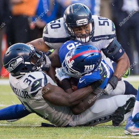 , 2017, Seattle Seahawks linebacker K.J. Wright (50) and safety Kam Chancellor (31) wrap up New York Giants running back Orleans Darkwa (26) on his run during the NFL game between the Seattle Seahawks and the New York Giants at MetLife Stadium in East Rutherford, New Jersey