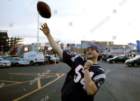 Keith Murray, of Cranston, R.I., tosses the football while tailgating in the parking lot of Gillette Stadium before an NFL football game between the New England Patriots and the Atlanta Falcons, in Foxborough, Mass