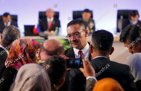 Malaysian Defense Minister Hishammuddin Hussein, center, chats with his staff prior to start of the 11th ASEAN Defense Ministers' Meeting in Clark, Pampanga province north of Manila, Philippines. The annual meeting, which the Philippines is hosting this year, also includes its dialogue partners such as United States, Australia, Japan, South Korea, New Zealand and India