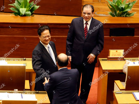 Former Vietnamese Prime Minister Nguyen Tan Dung, left, shakes hands with a member of the National Assembly as former General Secretary of the Communist Party Nong Duc Manh, right, looks on before the opening of the lawmaking body in Hanoi, Vietnam, . The country's gross domestic products expands 6.4 percent in the first nine months of this year and is expected to grow 6.7 percent this year