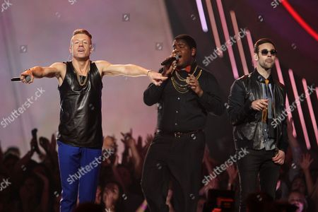 """Macklemore, left, and Ryan Lewis, right, perform """"Can't Hold Us"""" with Ray Dalton at the MTV Movie Awards in Sony Pictures Studio Lot in Culver City, Calif. Macklemore and Ryan Lewis are among the clear favorites as The Recording Academy prepares to unveil its Grammy nominees on . A handful will be unveiled during a CBS special, and the rest announced after it airs"""