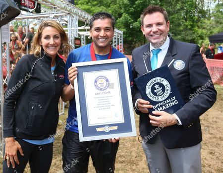 Delta Faucet company President, Jai Shah,(C) accepts GUINESS WORLD RECORDS title from Michael Empric (R) for most people showering simultaneously at the Indiana Warrior Dash event alongside Olympic Gold Medalist Summer Sanders on in Crawfordsville, Ind