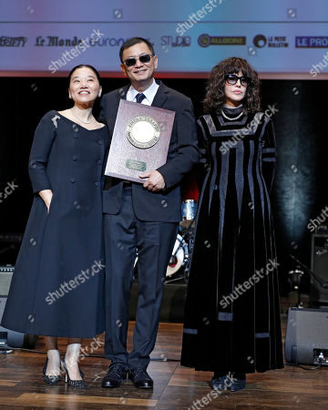 Hong Kong director Wong Kar-wai poses for photographers with his wife, Chan Ye-cheng, left, and French actress Isabelle Adjani, right, after receiving his award during the 9th Lumiere Festival Award ceremony, in Lyon, central France