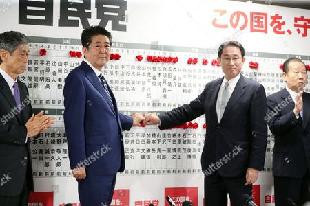 Japanese Prime Minister and ruling Liberal Democratic Party (LDP) president Shinzo Abe and Policy spealker Fumio Kishida pin a rosette on his party's candidates list in the Lower House election at the LDP headquarters in Tokyo on Sunday, October 22, 2017.