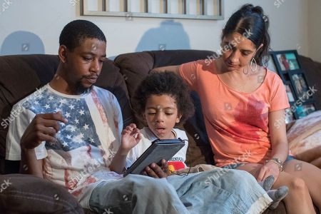 Stock Photo of Kenneth Hulett Jr., left, and Emily Bolton-Blatt, right, sit with their son, Kenneth Hulett III, as he plays a video game during an interview at their home in Queens, N.Y., on . Kenneth was one of 32 babies evacuated from NYU Langone hospital, after it flooded and lost power during Superstorm Sandy
