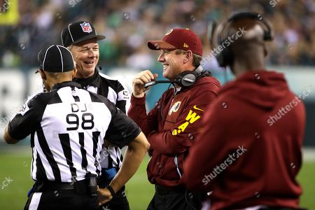 Washington Redskins head coach Jay Gruden, center right, laughs with back judge Scott Helverson (93) and head linesman Greg Bradley (98) during the first half of an NFL football game against the Philadelphia Eagles, in Philadelphia