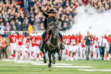 Laurie Tolboom, The Masked Rider, rides in with the Red Raiders following before the game against Oklahoma State at Jones AT&T Stadium in Lubbock, Texas