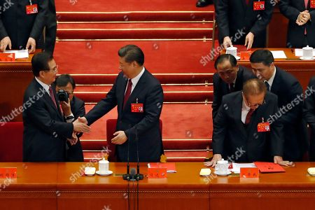 Xi Jinping, Hu Jintao, Jiang Zemin. Chinese President Xi Jinping, center, shakes hands with former President Hu Jintao, left, as former President Jiang Zemin, right, is assisted to stand during the closing ceremony for the 19th Party Congress held at the Great Hall of the People in Beijing
