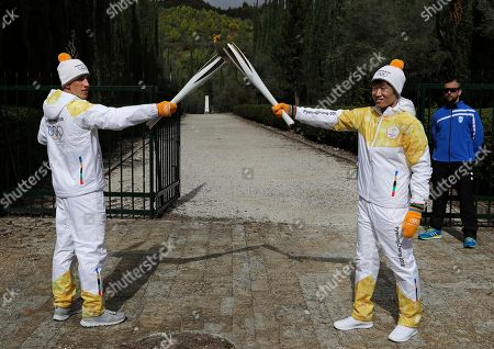 Torch bearer Greek cross-country skier Apostolos Angelis, left, passes the flame to the South Korean former soccer player Park Ji-Sung during the lighting ceremony of the Olympic flame in Ancient Olympia, southwestern Greece, on . The flame will be transported by torch relay to Pyeongchang, South Korea, which will host the Feb. 9-25, 2018 Winter Olympics