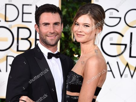 "Adam Levine, left, and Behati Prinsloo arrive at the 72nd annual Golden Globe Awards in Beverly Hills, Calif. A spokeswoman for ""The Voice"" coach says Levine and the Victoria's Secret model welcomed a daughter named Dusty Rose Levine. No other details were provided. The frontman for the band Maroon 5 and Prinsloo have been married since 2014"