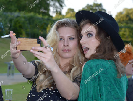 Models Chloe Hayward and Talulah Lennox take a picture at the 'Fashion Rules' Exhibition launch at Kensington Palace in London on