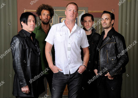 "Members of the band Queens of the Stone Age, from left, Troy Van Leeuwen, Jon Theodore, Josh Homme, Michael Shuman and Dean Fertita pose for a portrait at the Wiltern Theater, in Los Angeles. The band is releasing their first album in six years, ""... Like Clockwork,"" on June 4"