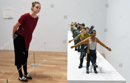 Stock Photo of A museum staff inside the 'Age of Terror: Art Since 9/11' exhibition, looks over an artwork titled 'Circadium Rhyme' by Indian artist Jitish Kallat at the Imperial War Museum in London, Britain, 25 October  2017. The exhibit runs from 26 October 2017 to 28 May 2018 and features works from films, sculptures, paintings, installation and photography. It is the first major exhibition to consider the artists' response to war and conflict since 9/11.