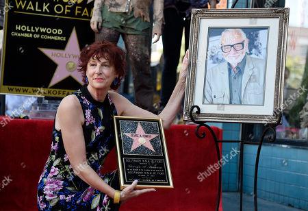 Suzanne Desrocher, the widow of late director George A. Romero, poses alongside a portrait of Romero