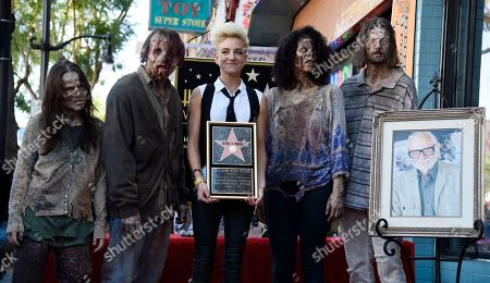 Tina Romero, center, daughter of the late director George A. Romero, poses with zombie characters