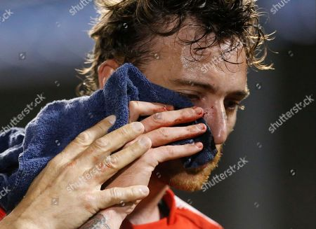 Argentina's Independiente Fernando Amorebieta leaves the pitch after he was hit in the face, during a Copa Sudamericana quarter final soccer game against Paraguay's Nacional, in Asuncion, Paraguay