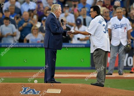 Vin Scully and Fernando Valenzuela throw out the ceremonial first pitch before Game 2 of baseball's World Series between the Houston Astros and the Los Angeles Dodgers, in Los Angeles