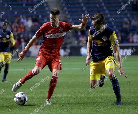 Luis Solignac, Damien Perrinelle. Chicago Fire forward Luis Solignac, left, controls the ball against New York Red Bulls defender Damien Perrinelle during the first half of an MLS soccer playoff game, in Bridgeview, Ill