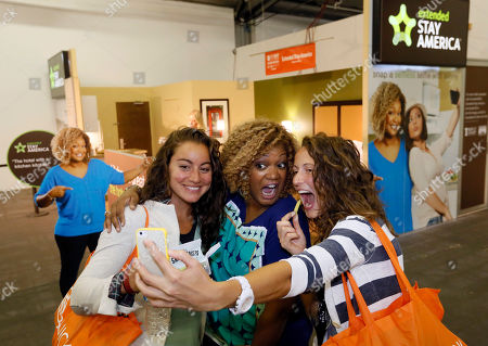 Food Network host Sunny Anderson, center, poses for a 'selfie' with fans outside the Extended Stay America traveling hotel room to donate to No Kid Hungry at the New York City Wine & Food Festival