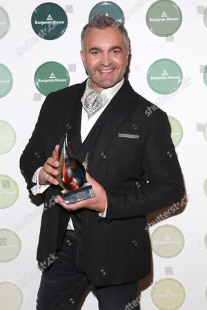 Stock Picture of Interior designer Martyn Lawrence Bullard poses with his Commercial Interior HUEY Award at the sixth annual Benjamin Moore HUE Awards on at the Highline Ballroom in New York