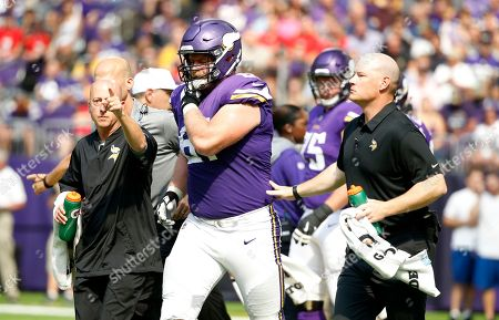 Stock Picture of Minnesota Vikings offensive guard Joe Berger (61) is helped off the field after getting injured during the first half of an NFL football game against the Tampa Bay Buccaneers, in Minneapolis