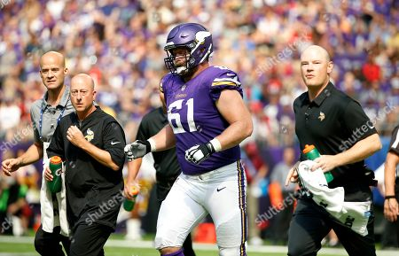 Minnesota Vikings offensive guard Joe Berger (61) is helped off the field after getting injured during the first half of an NFL football game against the Tampa Bay Buccaneers, in Minneapolis