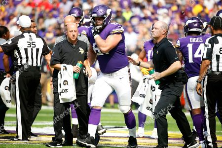Stock Image of Minnesota Vikings offensive guard Joe Berger (61) is helped off the field after getting injured during the first half of an NFL football game against the Tampa Bay Buccaneers, in Minneapolis