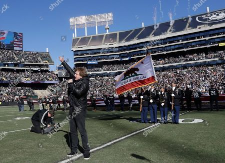 Singer Eddie Money performs the national anthem before an NFL football game between the Oakland Raiders and the Indianapolis Colts in Oakland, Calif