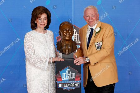 NFL team owner Jerry Jones, right, poses with a bust of himself and presenter, his wife, Gene Jones, during an induction ceremony at the Pro Football Hall of Fame, in Canton, Ohio