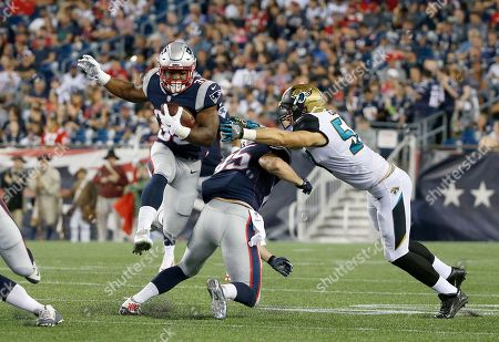 New England Patriots running back LeShun Daniels (39) hurdles teammate Sam Cotton as he delivers a block to a Jacksonville Jaguars player during an NFL preseason football game, in Foxborough, Mass