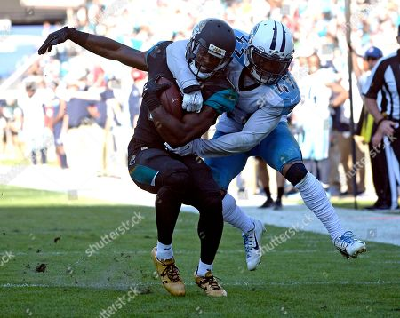 Jacksonville Jaguars wide receiver Marqise Lee. left, is tackled after a reception by Tennessee Titans defensive back Valentino Blake (47) during the second half of an NFL football game, in Jacksonville, Fla
