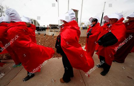 """Handmaids Tale protesters. Wearing red dresses and white bonnets represented in the dystopian novel by Margaret Atwood, """"The Handmaid's Tale,"""" protesters line the sidewalk outside a hotel where Vice President Mike Pence is scheduled to appear at in Greenwood Village, Colo., . Pence is scheduled to speak at a Republican Party fundraiser on Thursday"""