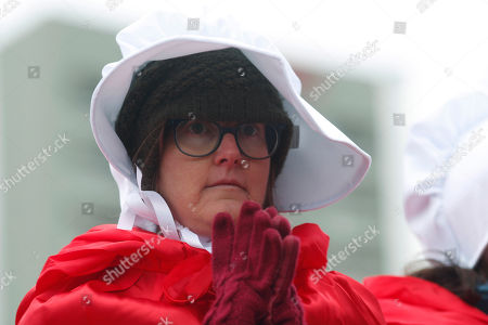 """Wearing red dresses and white bonnets represented in the dystopian novel by Margaret Atwood, """"The Handmaid's Tale,"""" April Allderdice of Denver joins protesters line the sidewalk outside a hotel in which Vice President Mike Pence is scheduled to appear at a fundraising event for Colorado Republicans in Greenwood Village, Colo., late"""