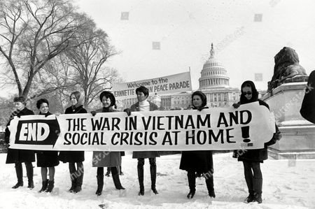 Members of a women's brigade hold a banner protesting the Vietnam War at a march led by former Montana congresswoman Jeannette Rankin in Washington, D.C. on Jan. 15, 1968.  Behind them are other protesters and the U.S. Capitol building. Carrying the sign, from left, are: Ruth Krause, Mrs. Vel Phillips, Wenn Griffin, Ruth Warwick, and Lucy Montgomery.  (AP Photo)