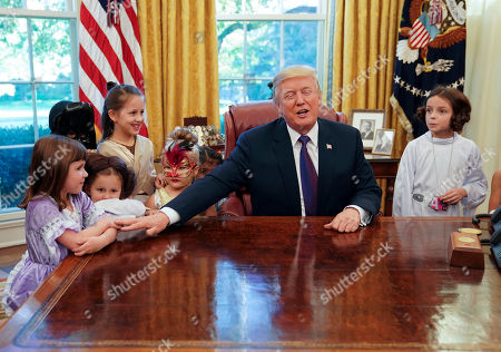 Stock Picture of Donald Trump, Claire Thomas. President Donald Trump reaches out to Claire Thomas, 5, far left, from Washington, before passing out candy to children dressed in their Halloween costumes in the Oval Office of the White House, . The White House had invited the children of members of the media to visit the president and to trick-or-treat on the White House complex of the Eisenhower Executive Office building