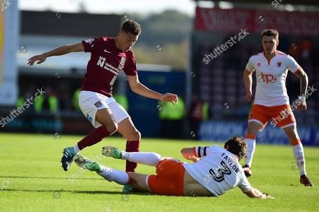 Blackpool defender Andy Taylor (3) slides in to tackle Northampton Town midfielder Shaun McWilliams (17) during the EFL Sky Bet League 1 match between Northampton Town and Blackpool at Sixfields Stadium, Northampton