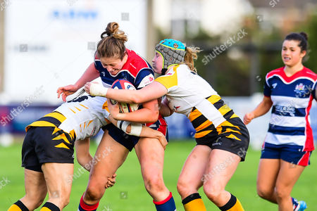 Amelia Buckland-Hurry of Bristol Ladies is tackled by Amy Cokayne and Kanyinsola Afilaka of Wasps Ladies