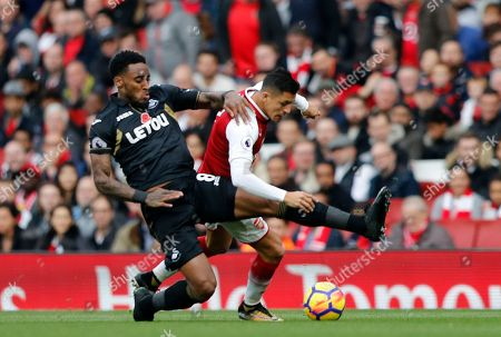 Arsenal's Alexis Sanchez, right, and Swansea's Leroy Fer challenge for the ball during the English Premier League soccer match between Arsenal and Swansea City at the Emirates stadium in London