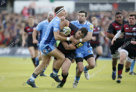 Brad Barritt of Saracens is tackled by Alex Lewington (with headband) and James Marshall of London Irish