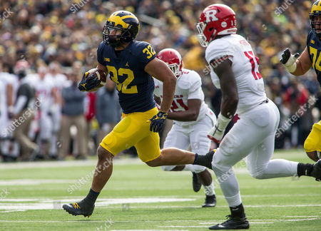 Ty Isaac, Ross Douglas, Trevor Morris. Michigan running back Ty Isaac (32) rushes past Rutgers linebacker Ross Douglas (21) and linebacker Trevor Morris (15) in the first quarter of an NCAA college football game in Ann Arbor, Mich
