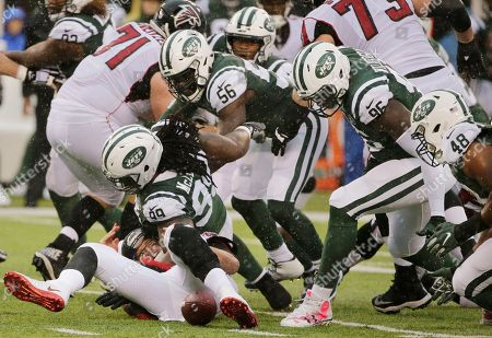 Atlanta Falcons quarterback Matt Ryan, bottom left, reacts after fumbling the ball as New York Jets' Jordan Jenkins (48), Muhammad Wilkerson (96) and Steve McLendon (99) close in during the first half of an NFL football game, in East Rutherford, N.J. Jenkins recovered the ball on the play