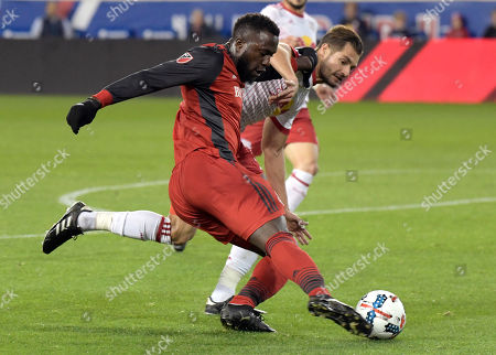 Stock Photo of Jozy Altidore, Damien Perrinelle. Toronto FC forward Jozy Altidore, left, passes the ball by New York Red Bulls defender Damien Perrinelle, right, during the first half of an MLS Eastern Conference semifinal soccer match, in Harrison, N.J