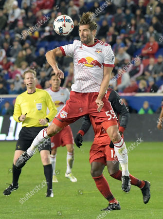 New York Red Bulls defender Damien Perrinelle (55) heads the ball during the first half of an MLS Eastern Conference semifinal soccer match against the Toronto FC, in Harrison, N.J