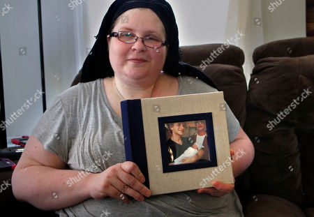 """Bethany Miller poses for a photo as she holds a photo album with her late son Kyle Wilson and his daughter on the cover in Jay, Maine. Miller said her son, who died from a diabetic coma, would've been among those in Maine who could benefit if voters on Nov. 7 demand a Medicaid expansion. """"He had a job, but he didn't make enough money to pay for his basic needs and his insulin, and he couldn't live without his insulin,"""" said Miller"""