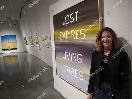 UNSETTLED ART-GREATER WEST. JoAnne Northrup, curator for contemporary arts at the Nevada Museum of Art poses in Reno, Nev., next to one of the works by American artist Ed Ruscha, ''Lost Empires Living Tribes,'' in the exhibit ''Unsettled.'' Northrup said it offers a new look at a ''super region'' called the ''Greater West.'' It stretches from Alaska down the West Coast to Patagonia, Antarctica, and across the Pacific to Australia